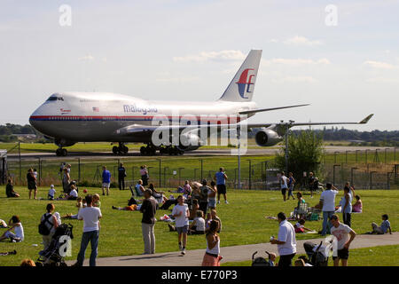 Malaysia Airlines Boeing 747-400 taxis past hundreds of spectators at Manchester airport. - Stock Photo