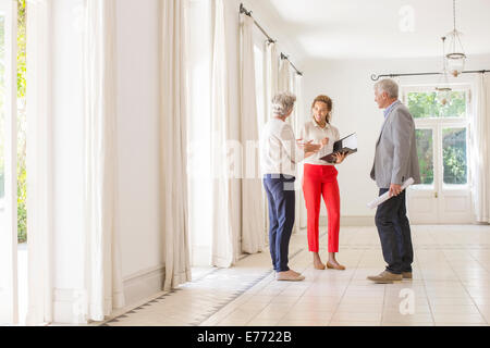 Older couple talking with woman in living space - Stock Photo