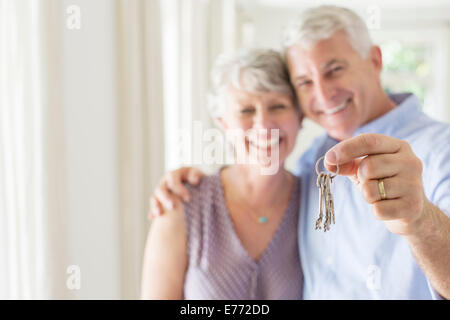 Older man holding keys with wife - Stock Photo
