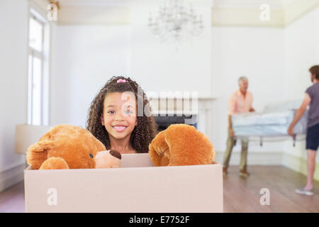 Young girl carrying box with teddy bear inside - Stock Photo