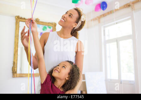 Mother and daughter holding balloons together - Stock Photo