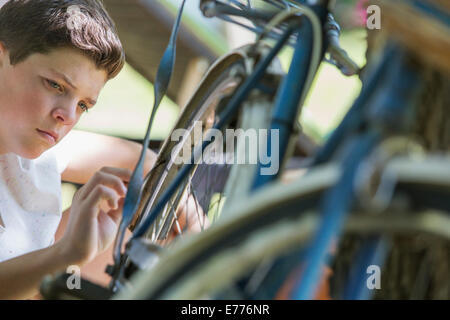 Young boy examining bicycle outdoors - Stock Photo