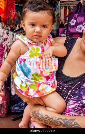 Honolulu Hawaii Hawaiian Oahu Chinatown Kekaulike Street market baby grandmother holding girl - Stock Photo