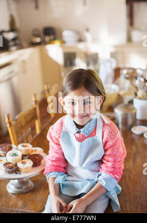 Young girl sitting on kitchen table near cupcakes - Stock Photo