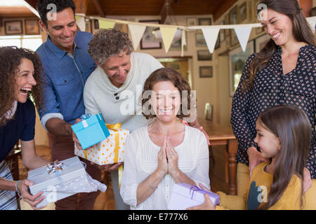 Older woman being given gift by family - Stock Photo