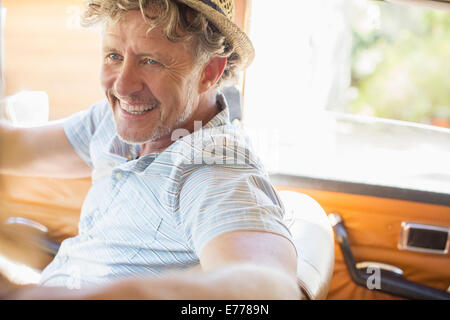 Older man driving car on sunny day - Stock Photo