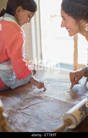 Mother and daughter playing in flower together - Stock Photo