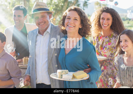 Older couple hugging at family picnic - Stock Photo
