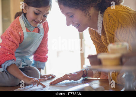 Mother and daughter playing in flour together - Stock Photo
