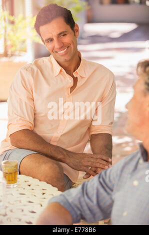 Father and son sat at table enjoying the outdoors - Stock Photo