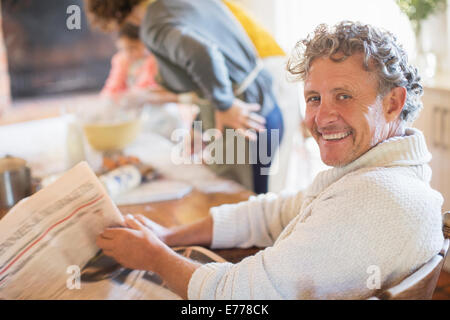 Older man reading news paper in kitchen - Stock Photo
