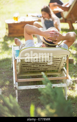 Older man relaxing on lawn chair - Stock Photo