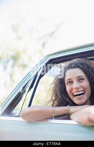 Woman relaxing on car door during car ride - Stock Photo