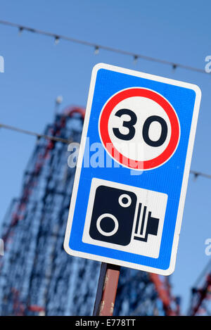 30 MPH speed limit and speed camera sign with 'The Big One' rollercoaster in the background (Blackpool, Lancashire) - Stock Photo