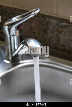 Water flowing from tap in kitchen sink - Stock Photo