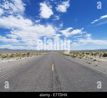 an empty desert road cuts across Nevada to the horizon under a partly cloudy blue sky