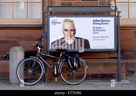 A bicycle attached to an advert for a John Byrne exhibition at the Scottish National Portrait Gallery in Edinburgh, - Stock Photo