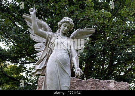Statue of an angel holding a flower and pointing to heaven in the Grange Cemetery Edinburgh, Scotland. - Stock Photo