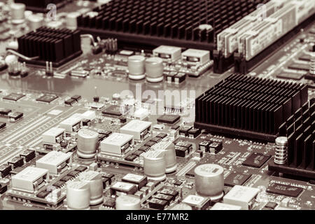 Circuit board of a powerful server computer with chips, capacitors, memory, and heat sinks visible - Stock Photo