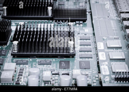 Circuit board of a powerful server computer with chips, capacitors, and heat sinks visible - Stock Photo