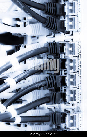Ethernet cables plugged into a high end router machine at a computer data center - Stock Photo