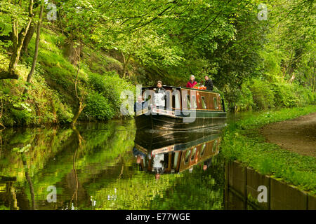Group of people on narrowboat on Llangollen canal in Wales with boat and surrounding emerald woodlands reflected - Stock Photo