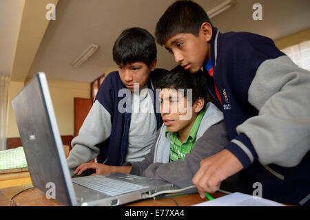 Three boys in a children's home are working together on a laptop, Ayacucho, Ayacucho region, Peru - Stock Photo