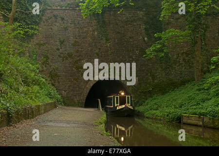 Narrow boat below high wall and surrounded by emerald vegetation as it emerges from Chirk tunnel on Llangollen canal, - Stock Photo