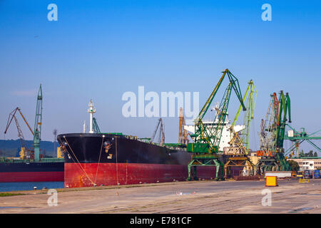 Big industrial cargo ship is loading in port of Varna - Stock Photo