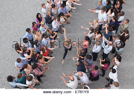 Woman walking between two groups of people, people clapping - Stock Photo