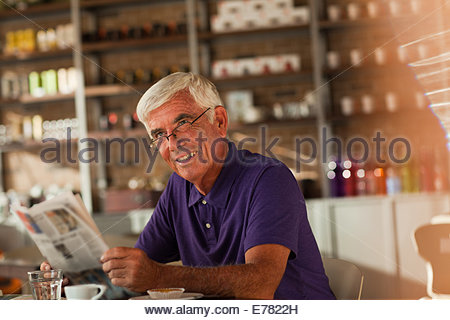 Man reading newspaper in cafe - Stock Photo