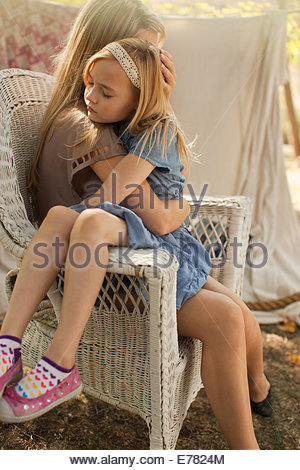 Mother hugging daughter outdoors - Stock Photo