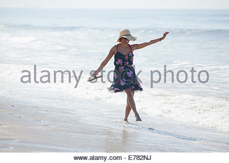 Woman carrying sandals on beach - Stock Photo