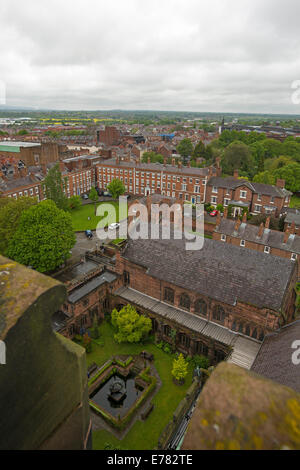 View of vast urban landscape, historic buildings, and gardens from high roof of cathedral in English city of Chester