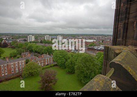 View of vast urban landscape dominated by high rise buildings from roof of historic cathedral in English city of Chester