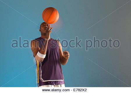 Basketball player balancing ball on one finger - Stock Photo
