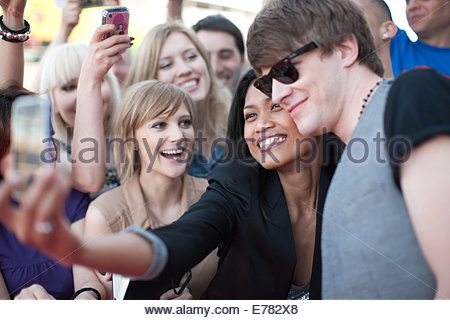 Fan taking picture of herself with celebrity - Stock Photo