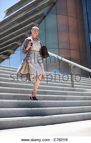 Businesswoman with coffee walking down steps outdoors - Stock Photo