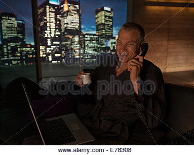 Man in bathrobe with laptop drinking coffee and talking on telephone - Stock Photo