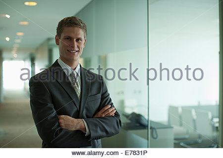 Businessman with arms crossed in office corridor - Stock Photo