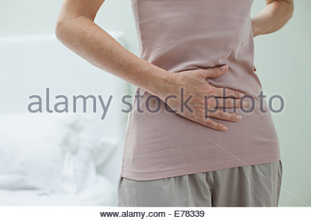 Woman rubbing aching stomach - Stock Photo