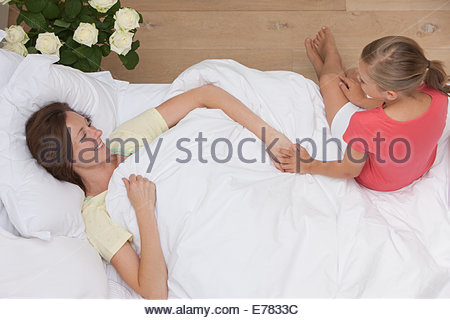 Mother laying in bed  with daughter holding hand - Stock Photo