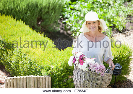 Woman carrying basket of flowers in garden - Stock Photo