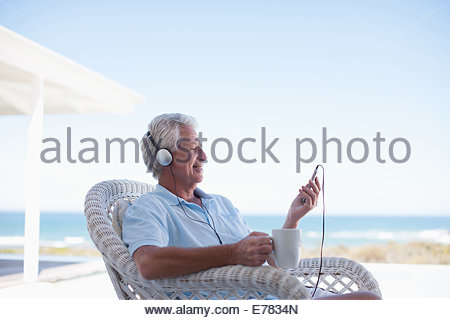 Senior man listening to mp3 player - Stock Photo