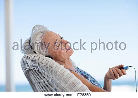 Senior woman listening to music on mp3 player - Stock Photo