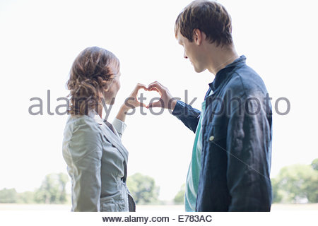 Smiling couple using hands to make heart shape - Stock Photo