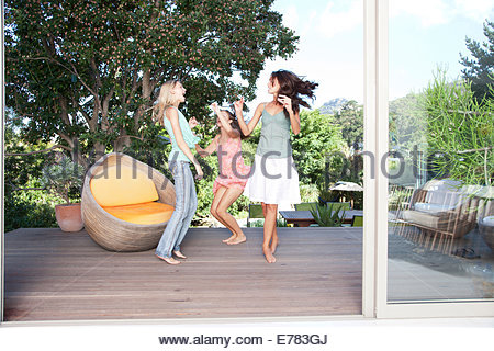 Friends dancing around on a deck - Stock Photo
