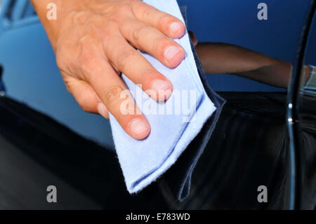 closeup of the hand of a young man polishing a car - Stock Photo