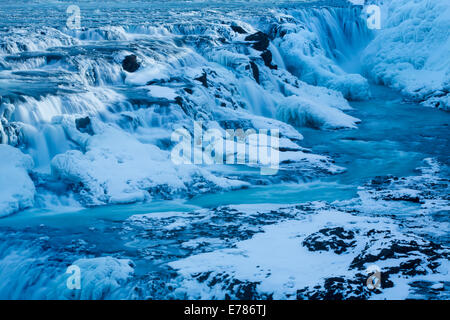 Gullfoss in winter with the frozen waterfall in the canyon of Hvítá River, southwest Iceland - Stock Photo