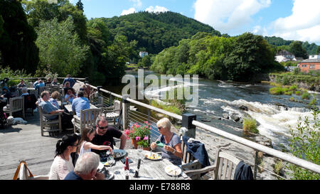 People eating al fresco at the Corn Mill restaurant on the River Dee in summer Llangollen Denbighshire North Wales - Stock Photo